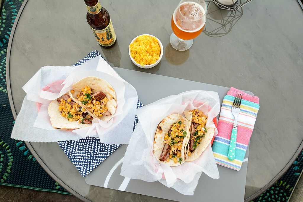 Overhead photo of Grilled Carne Asada Tacos and beers and corn salad on a table