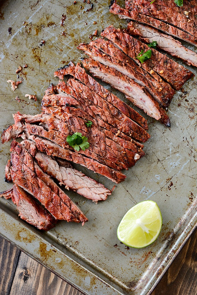 Grilled Carne Asada on a sheet pan with a lime