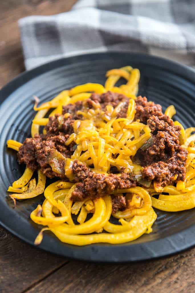 Side angle of Easy Skillet Cincinnati 'Skyline' Chili with Butternut Squash Noodles on a textured black plate with a gray and white checkered napkin