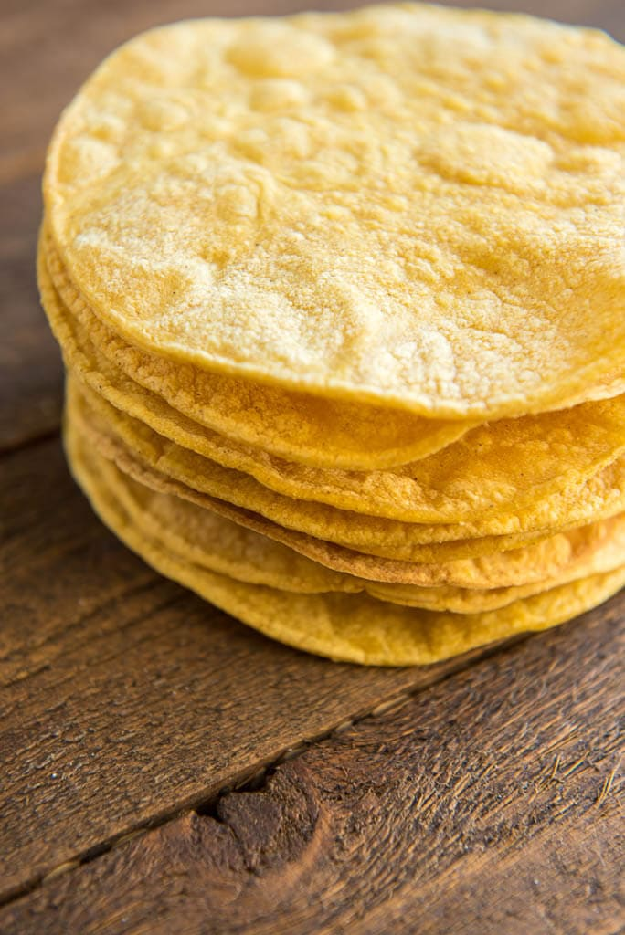 Baked corn tortillas in a stack for Crispy Chickpea Tostadas