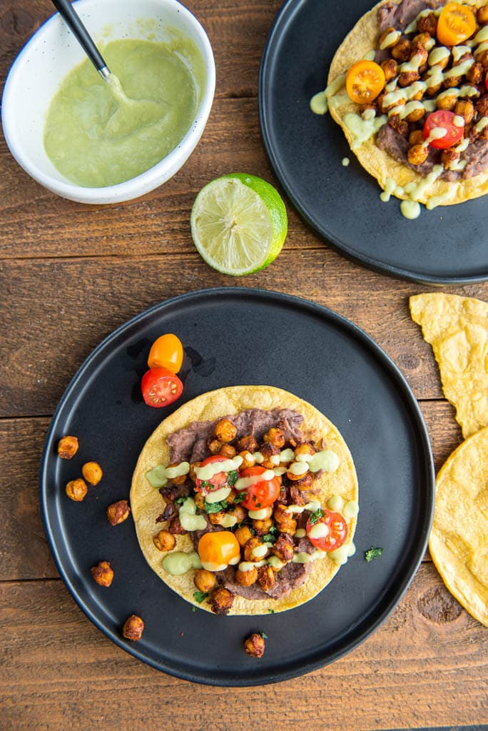 Overhead shot of two Black Plates with Crispy Chickpea Tostadas and garnished with tomatoes and avocado drizzle