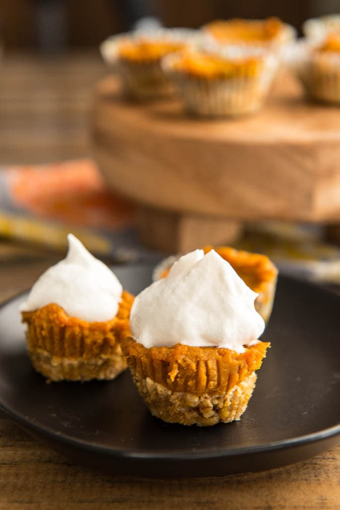 Mini Pumpkin Pies on black plate with extra pies in background