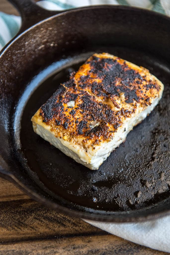 Cast iron pan with cooked blackened fish for Pan Seared Halibut Recipe with Pineapple Salsa.