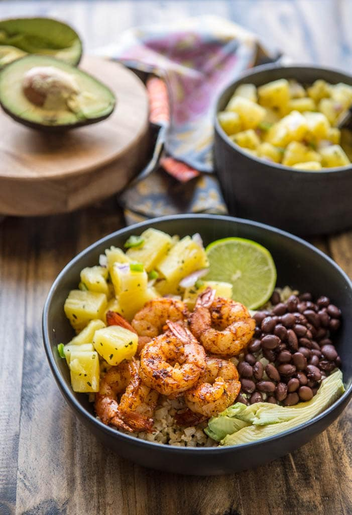 A black bowl filled with Shrimp Tacos in a Bowl with Pineapple Salsa, avocado, black beans and lime.
