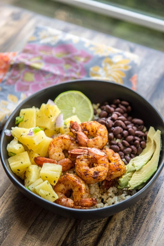 Black bowl and floral napkin with Shrimp Tacos in a Bowl with Pineapple Salsa plus black beans and avocado.