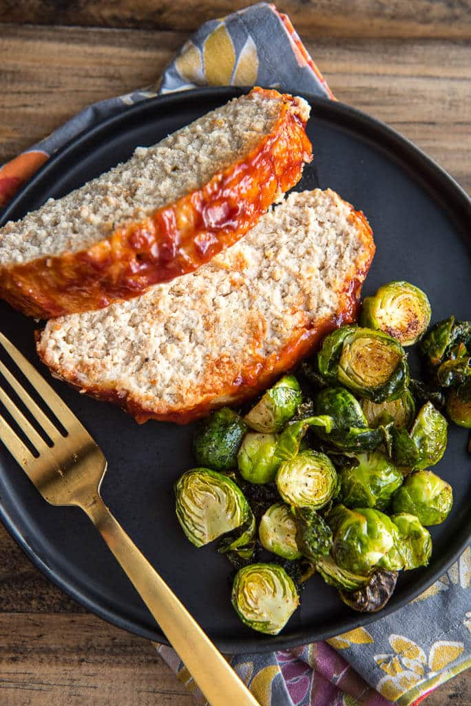 Sliced turkey meatloaf on a black plate with Brussels sprouts and a gold fork.