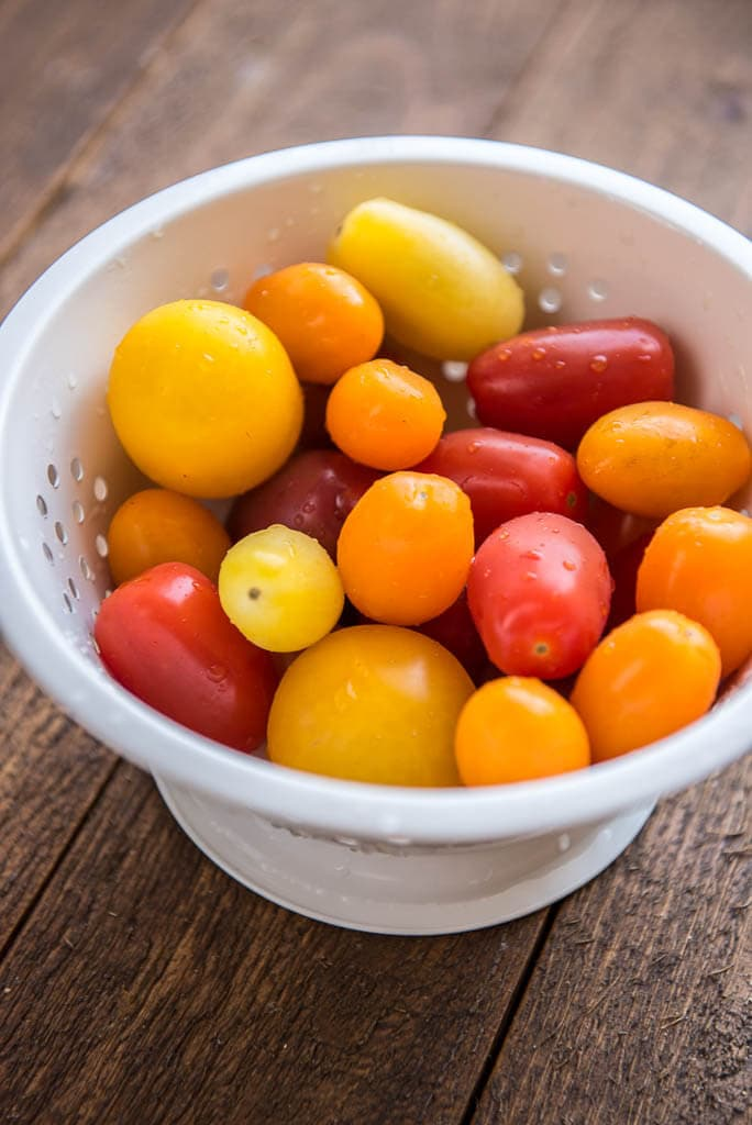 Red, orange and yellow baby tomatoes in a white colander for Wedge Salad with Herbed Buttermilk Dressing.
