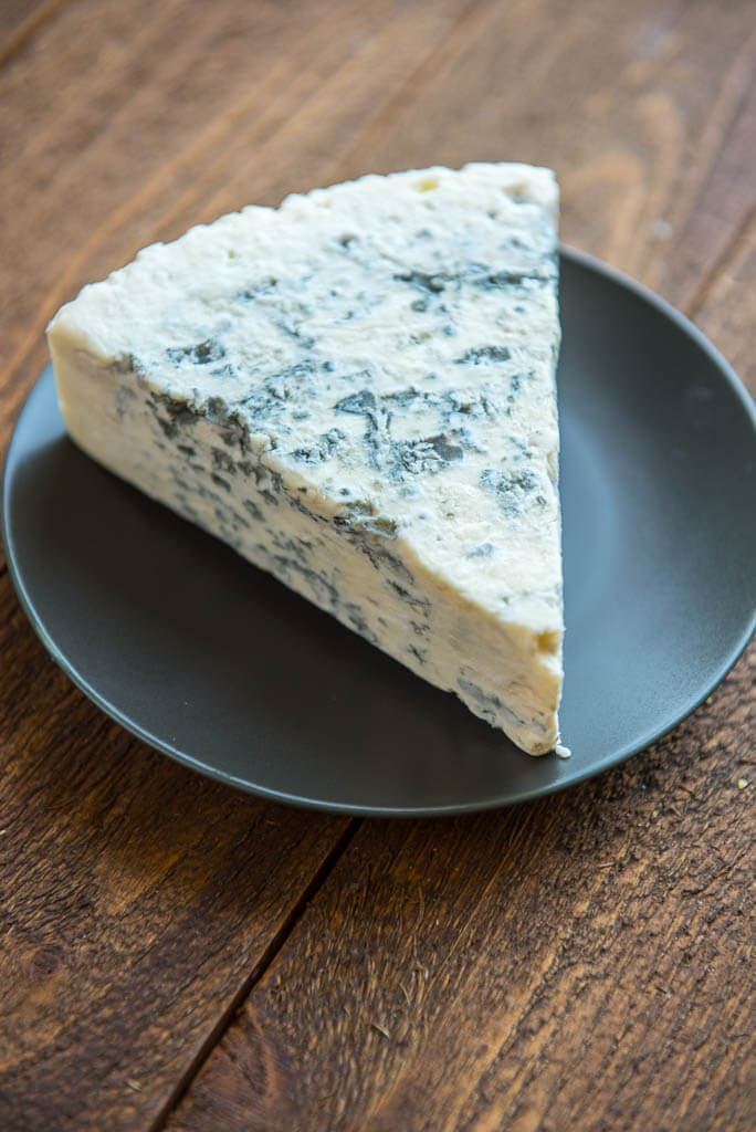 A wedge of gorgonzola cheese and a gray plate for Wedge Salad with Herbed Buttermilk Dressing.