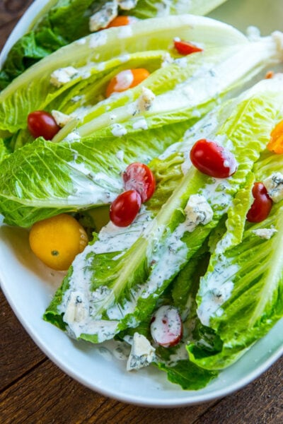 Romaine wedge salad with tomatoes and buttermilk dressing on a white platter.