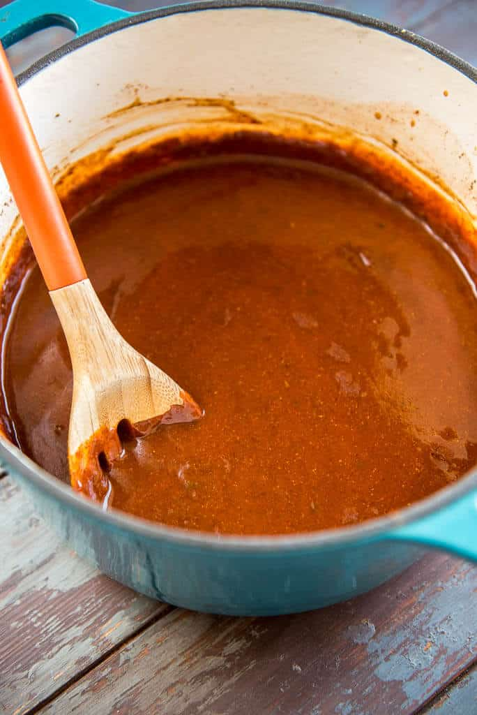 Homemade enchilada sauce in blue dutch oven with wooden spoon
