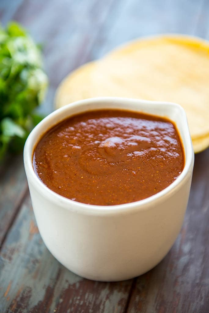 Homemade Enchilada Sauce in white bowl on wood table with tortillas