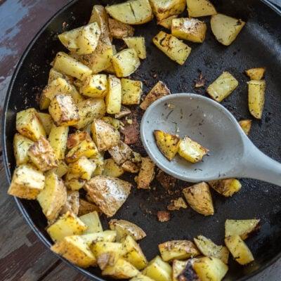 Breakfast Potatoes in cast iron skillet on wooden table