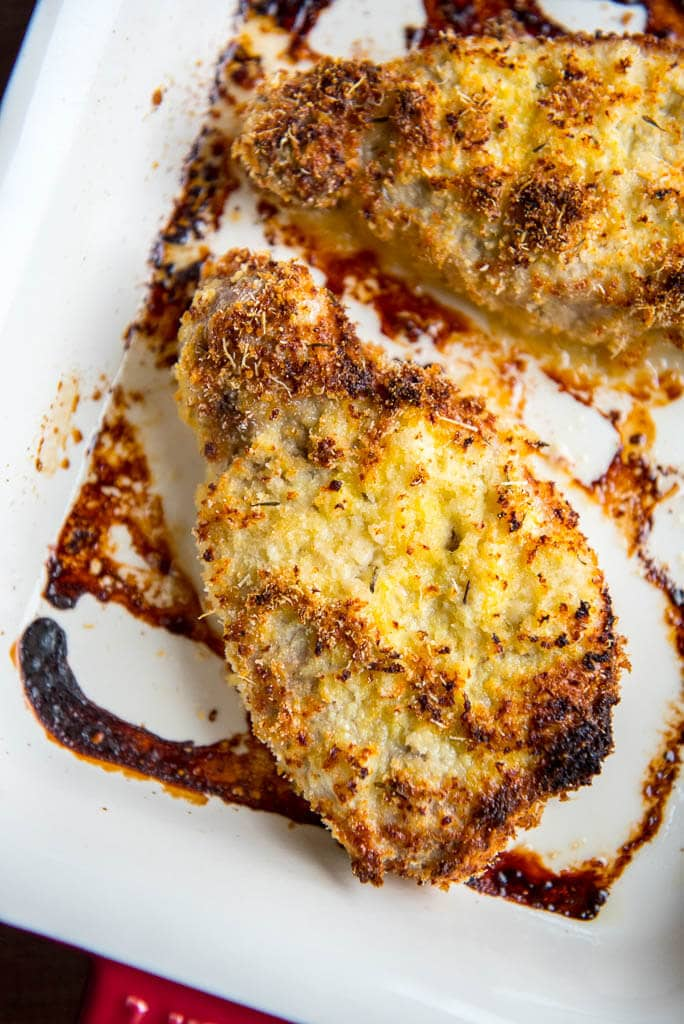 Parmesan Oven Baked Pork Chops in red and white casserole dish