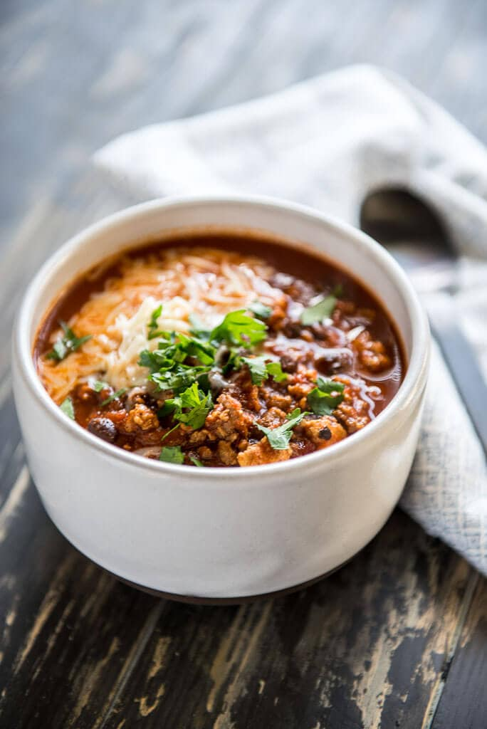 The Best IPA Beer Chili in a white bowl on a wood table