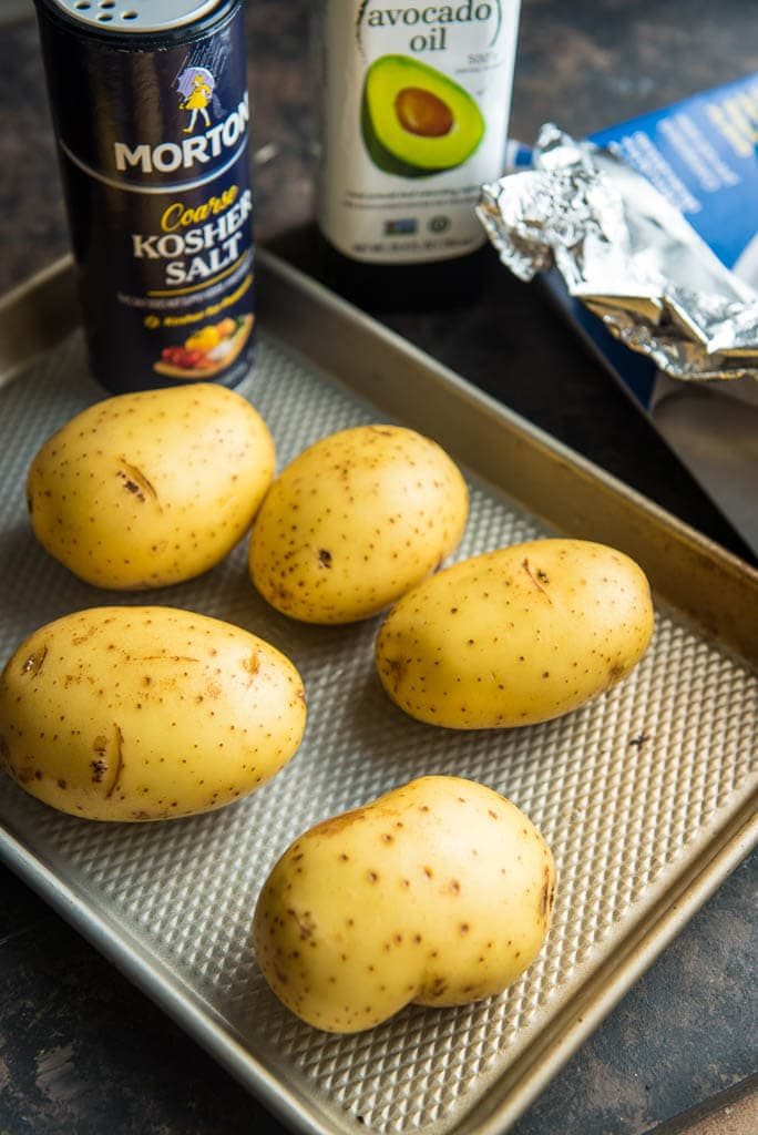 5 potatoes on a baking sheet ready to coat with olive oil and kosher salt