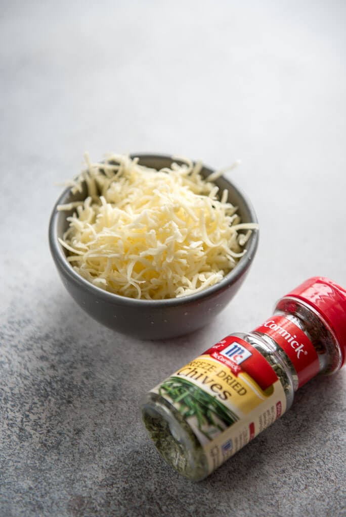 shredded white cheese in gray bowl next to jar of chives for Instant Pot Sous Vide Egg Bites