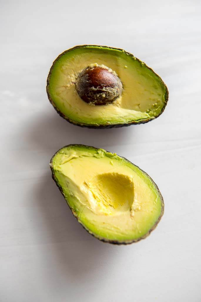 avocado cut in half on white countertop