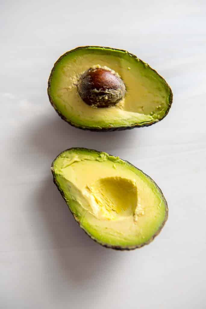 avocado halves on white table