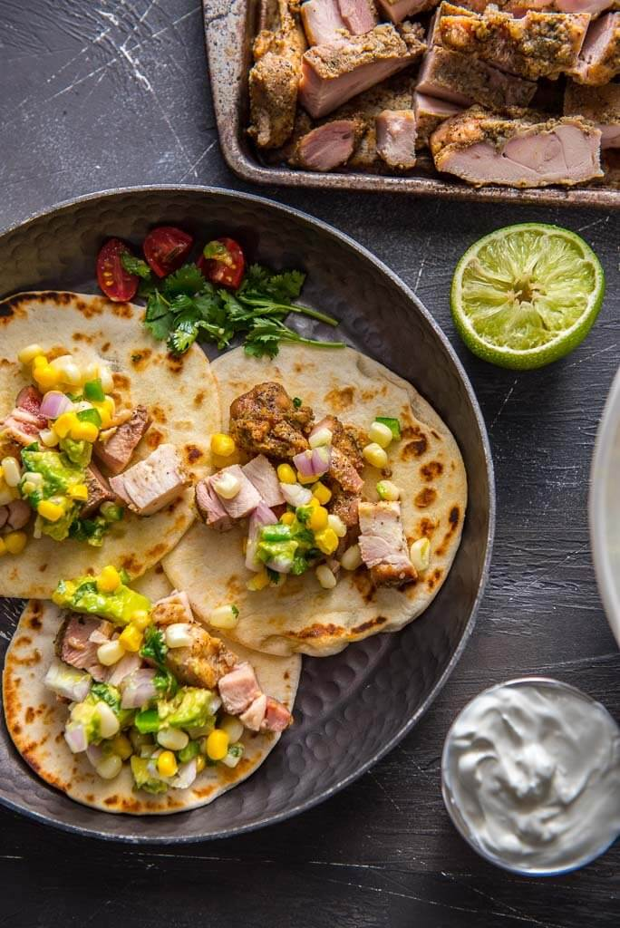 chicken street tacos on metal plate topped with avocado corn salsa