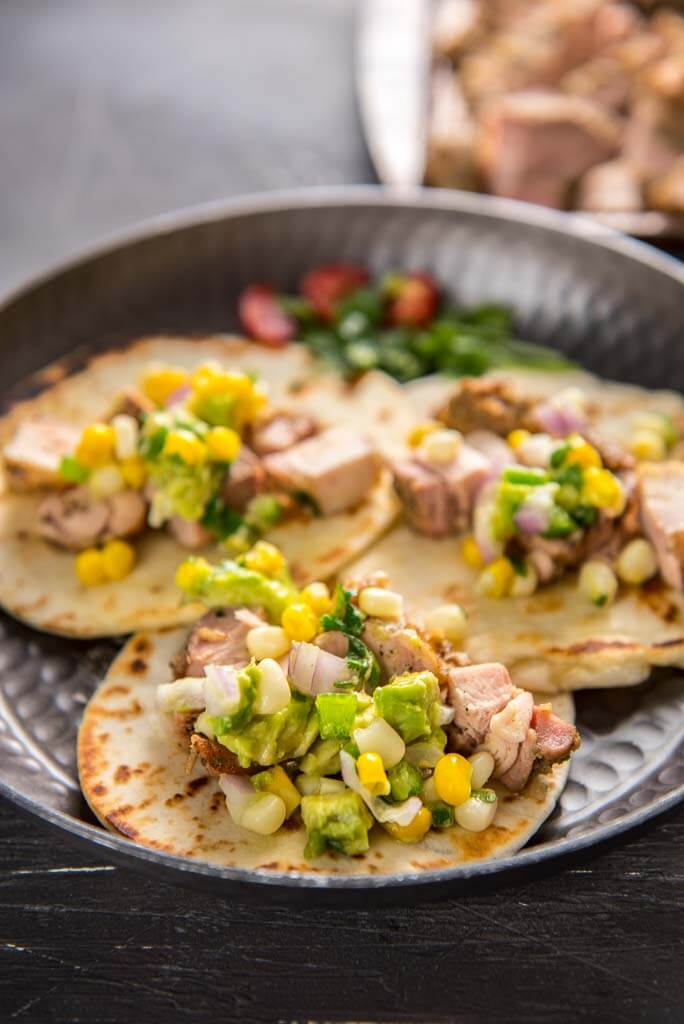 grilled chicken tacos with avocado salsa on metal plate
