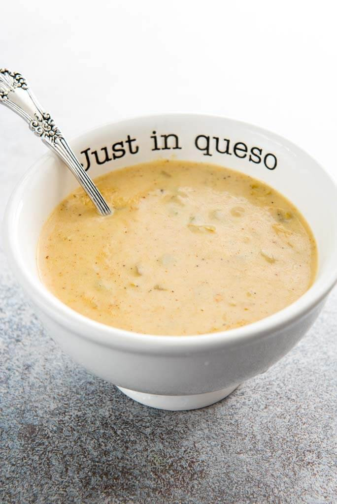 queso blanco dip in white bowl that says just in queso on the rim