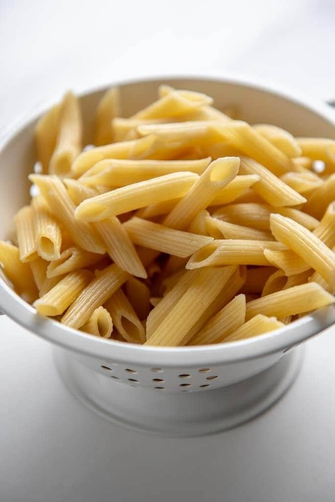 penne pasta in a white colander