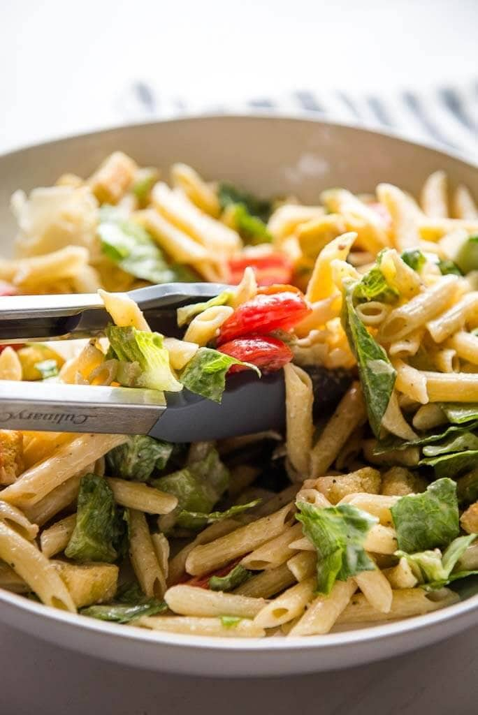tossing together ingredients for caesar pasta salad using tongs in white bowl