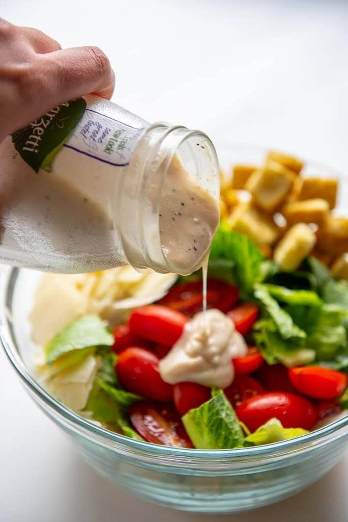 caesar dressing being poured over ingredients for caesar pasta salad