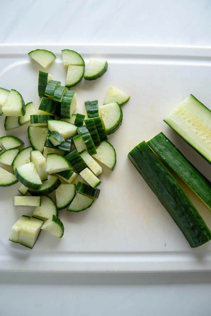 English cucumber chopped on white cutting board