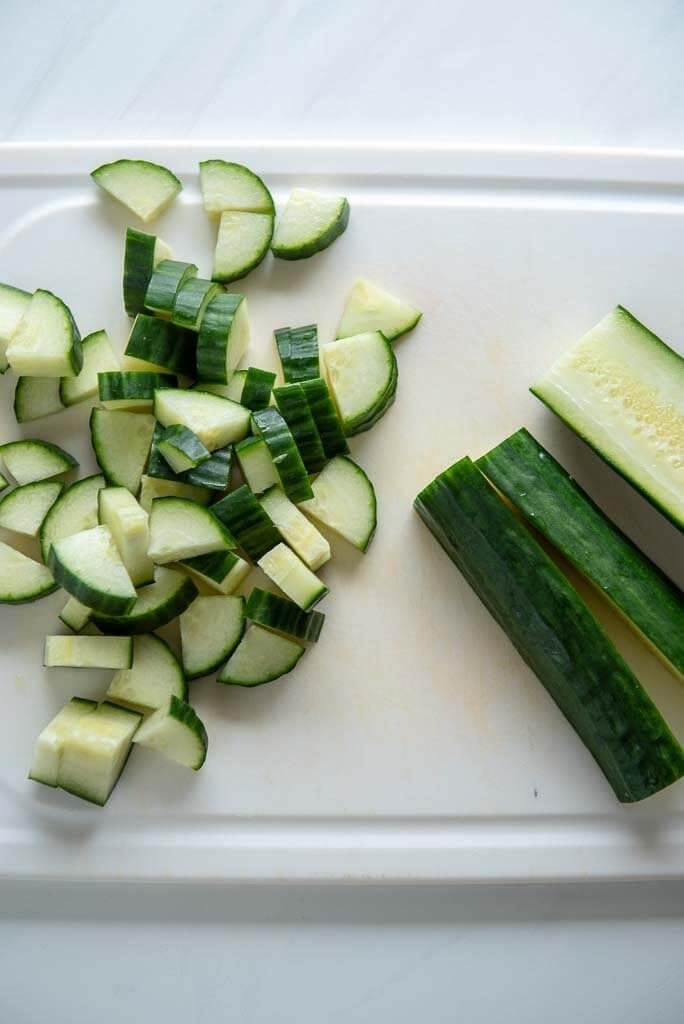 English cucumber chopped on white cutting board
