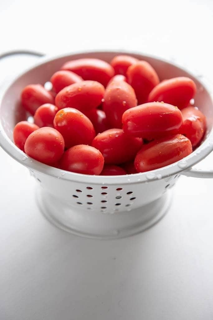 grape tomatoes in a white colander
