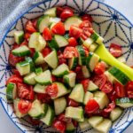 cucumber tomato salad in a blue and white serving bowl with a green spoon