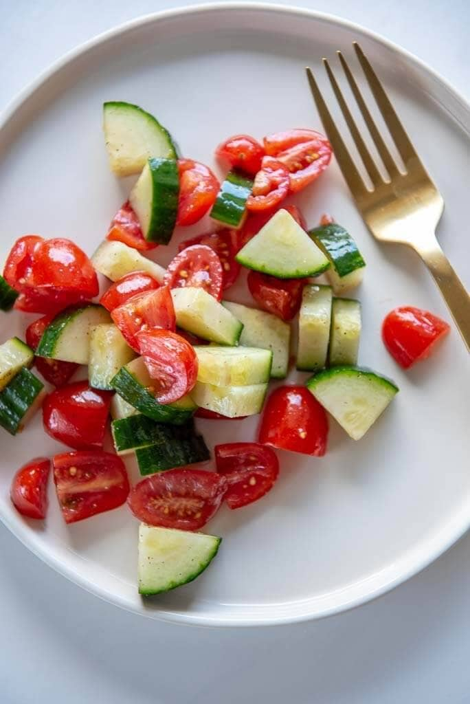 cucumber and tomato salad on a white plate with a gold fork