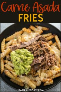 The snack that is also hearty enough to be a meal! Delicious Carne Asada Fries are topped with homemade queso blanco dip plus my an easy guacamole and tender carne asada for a dish that can be served up at a tailgate party or for dinner! #garnishedplate #carneadada #fries #cheesefries