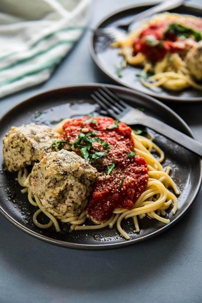 turkey meatballs on top of spaghetti with marinara on gray plates topped with cheese and parsley