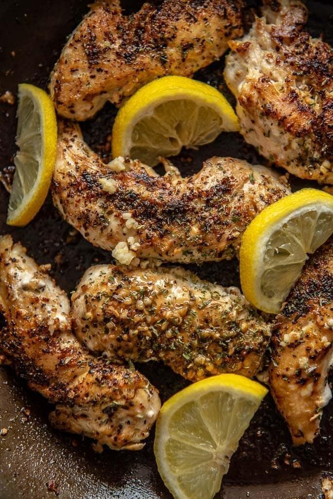 lemon basil chicken in skillet topped with lemon slices