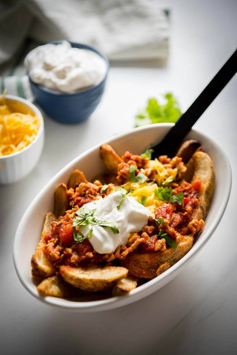 chili cheese fries topped with sour cream in a white oval bowl with black fork