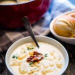 creamy potato soup topped with bacon crumbles with a side of rolls