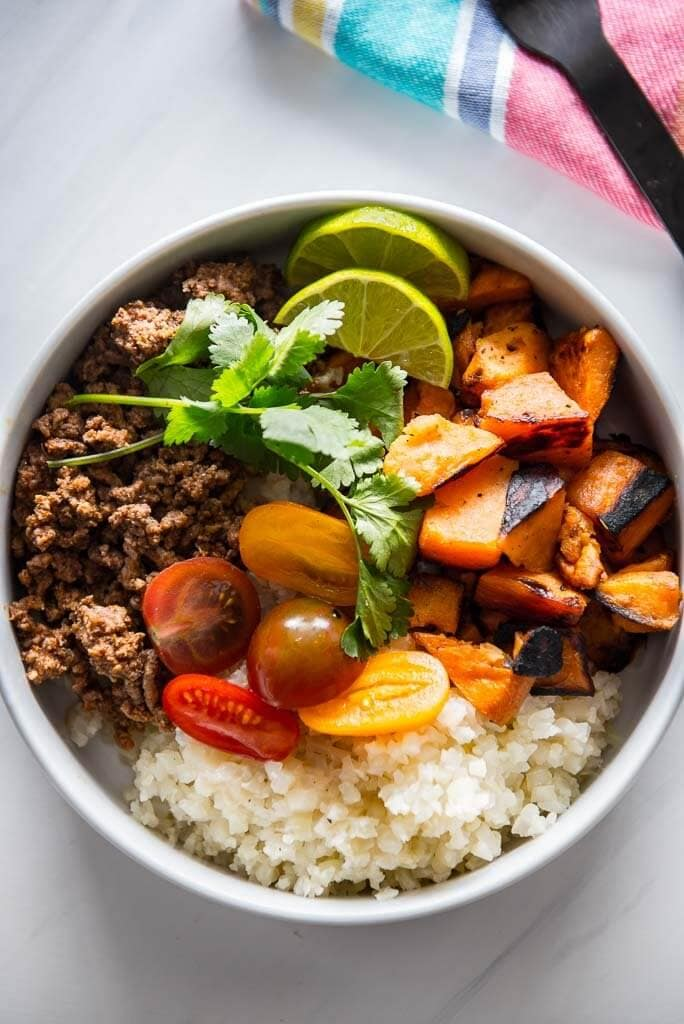 healthy taco bowl with sweet potato, cauliflower rice, beef, tomatoes and cilantro