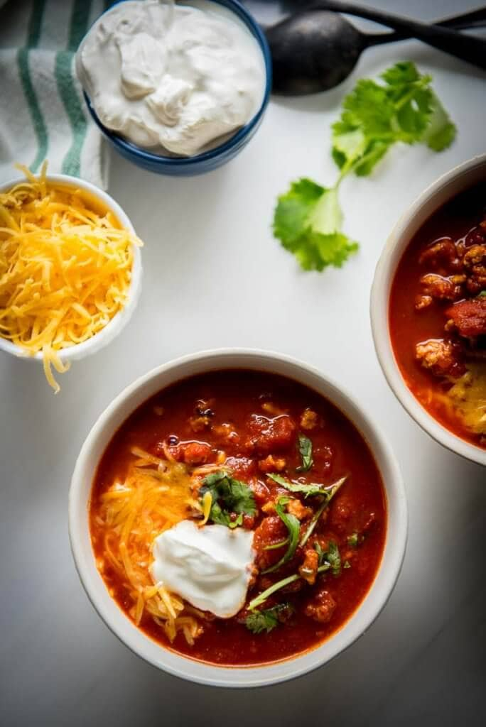 2 white bowls full of smokey chicken chili topped with cheese and sour cream