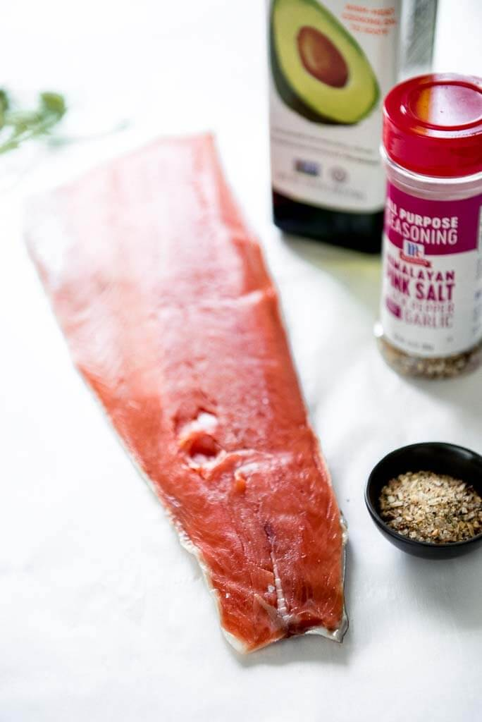 a filet of salmon along with oil and spices to rub for oven baked salmon