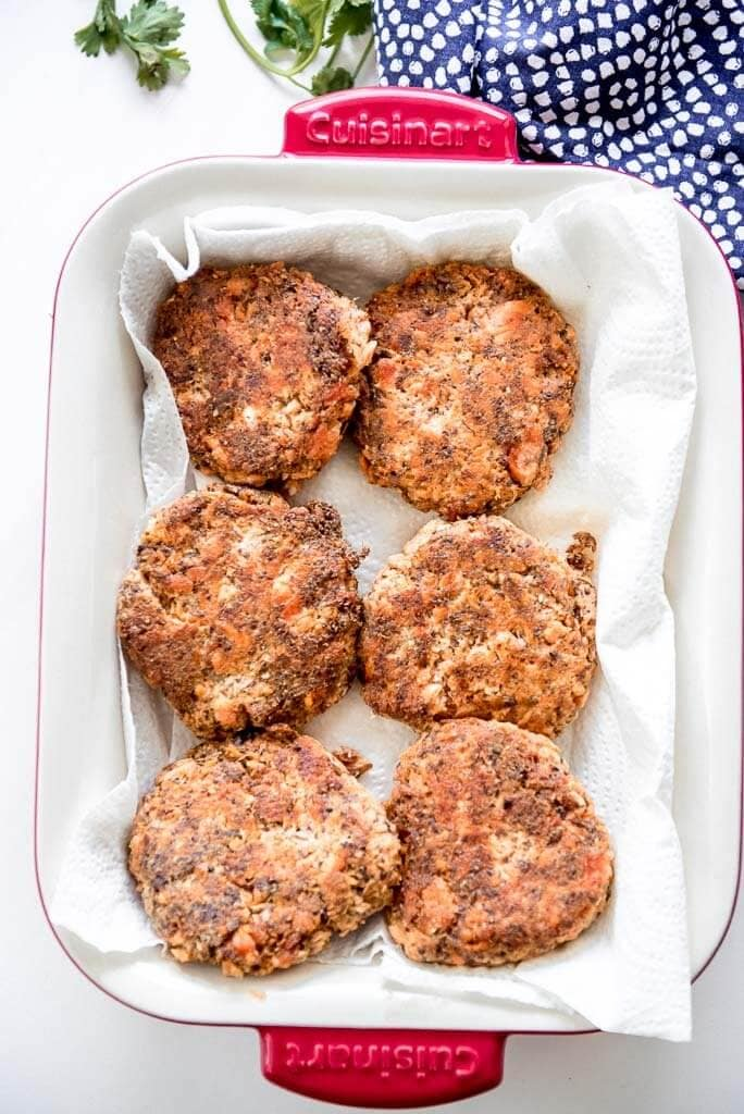 6 salmon patties in a rectangle red casserole dish on paper towels