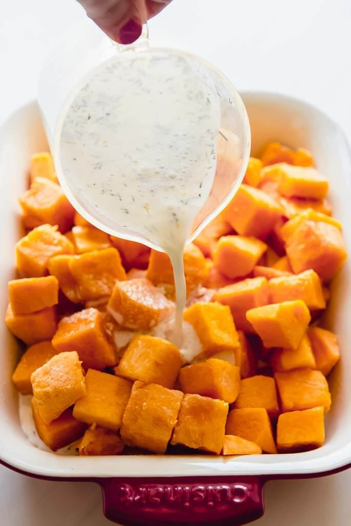 cubed butternut squash in a casserole dish with cream sauce being poured on top