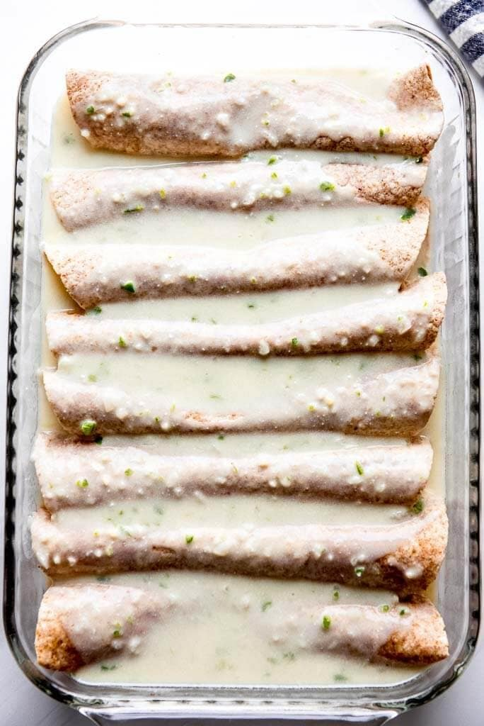 chicken enchiladas being assembled in casserole dish topped with white sauce