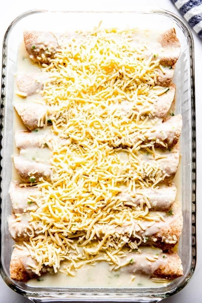 chicken enchiladas ready to bake in glass casserole dish topped with white shredded cheese