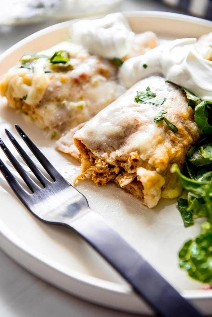 chicken enchiladas topped with white sauce cut open with fork