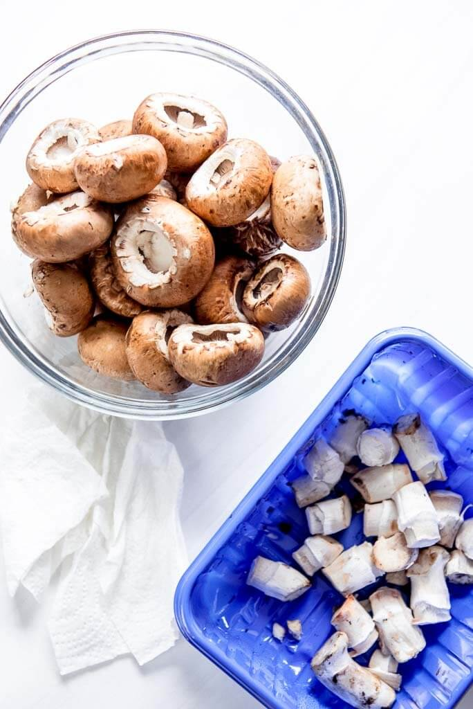 bowl of mushrooms with stems removed to separate plastic carton
