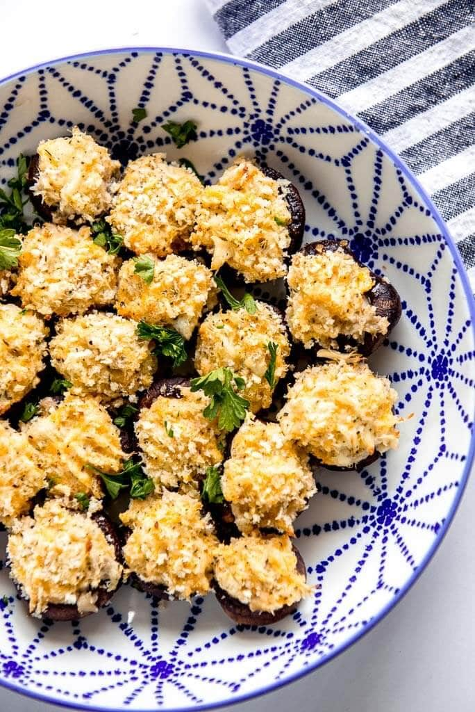 blue and white decorated bowl full of crab stuffed mushrooms