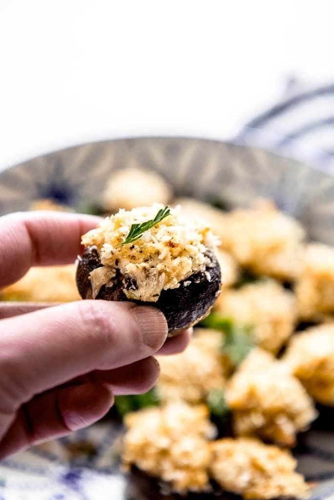 one stuffed mushroom in hand held above bowl of mushrooms