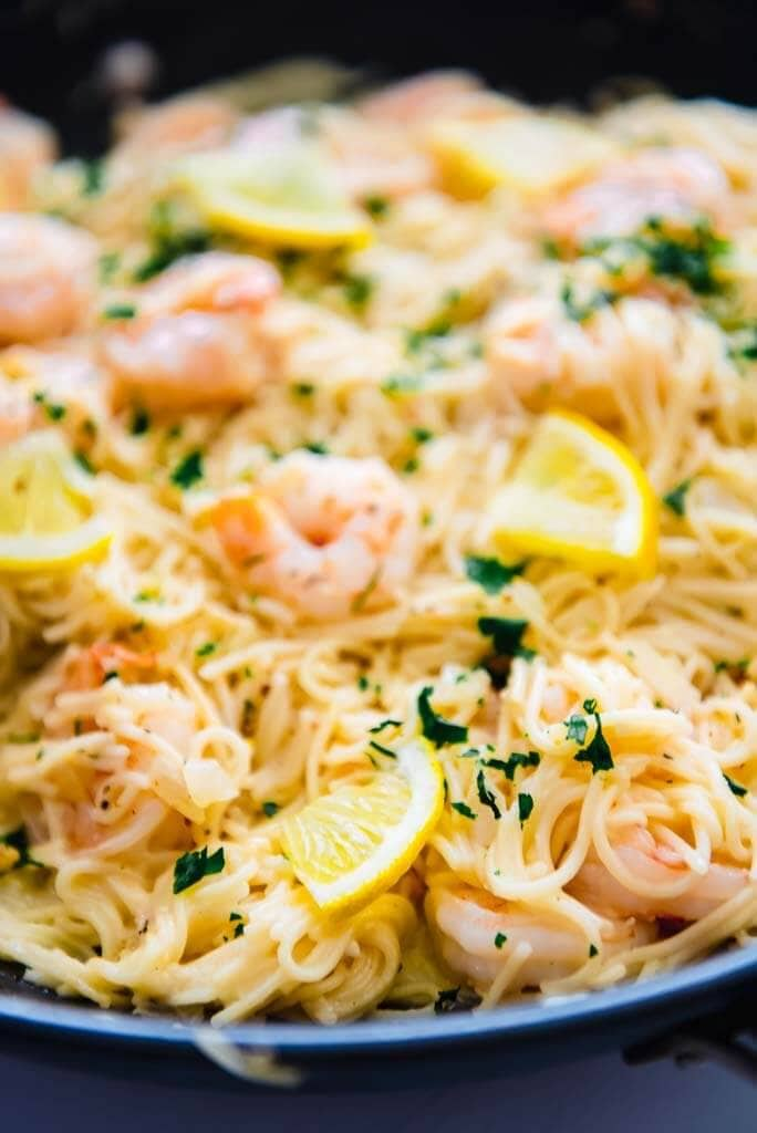 lemon garlic shrimp pasta in round skillet topped with lemon slices